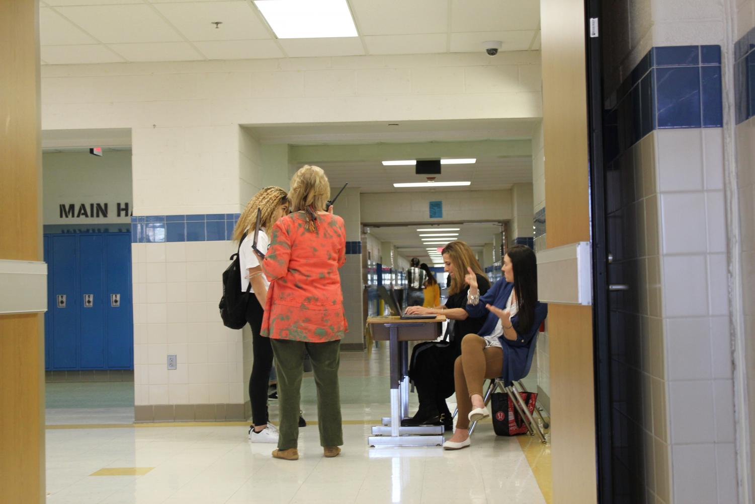 Systems of Support staff Donna Spitzer and Amy Lee as well as counselor Jennifer Rogin-Marks write out a pass for a late student.