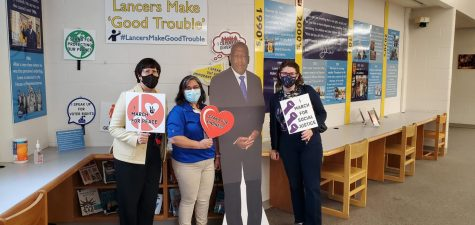 Library staff Mimi Marquet, Lourdes Salas, and Lisa Koch pose in front of a paper cut-out of Rep. John Lewis during the John R. Lewis High School Rededication Ceremony, April 23, 2021.